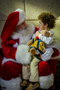 Curly hair boy looking at Santa